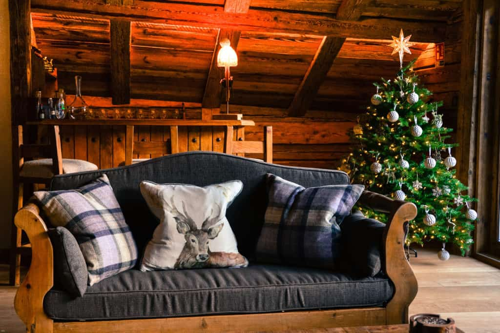 Cocktail bar, sofa with red deer cushion with Christmas tree behind