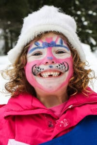 facepaint on a child outside in the snow