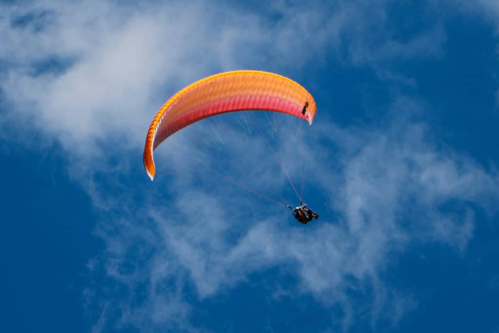 Paragliding in the sky with clouds behind