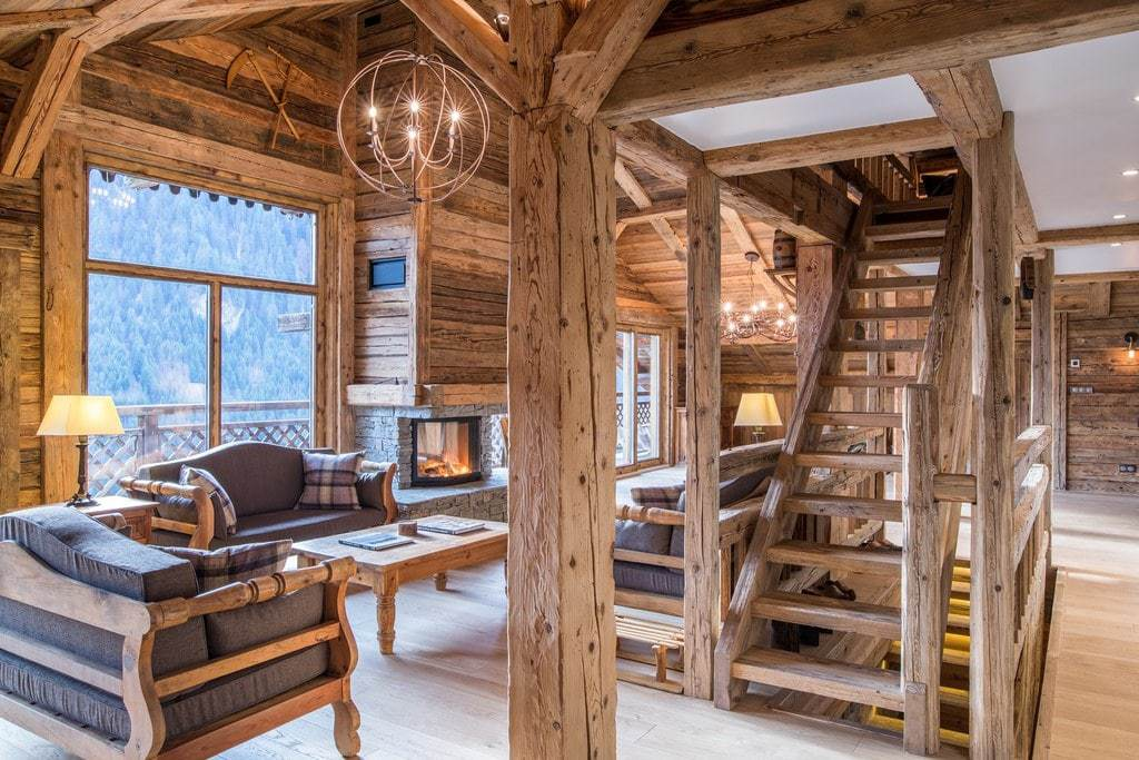 The living room with log fire of La Grange au Merle by Clarian Chalets