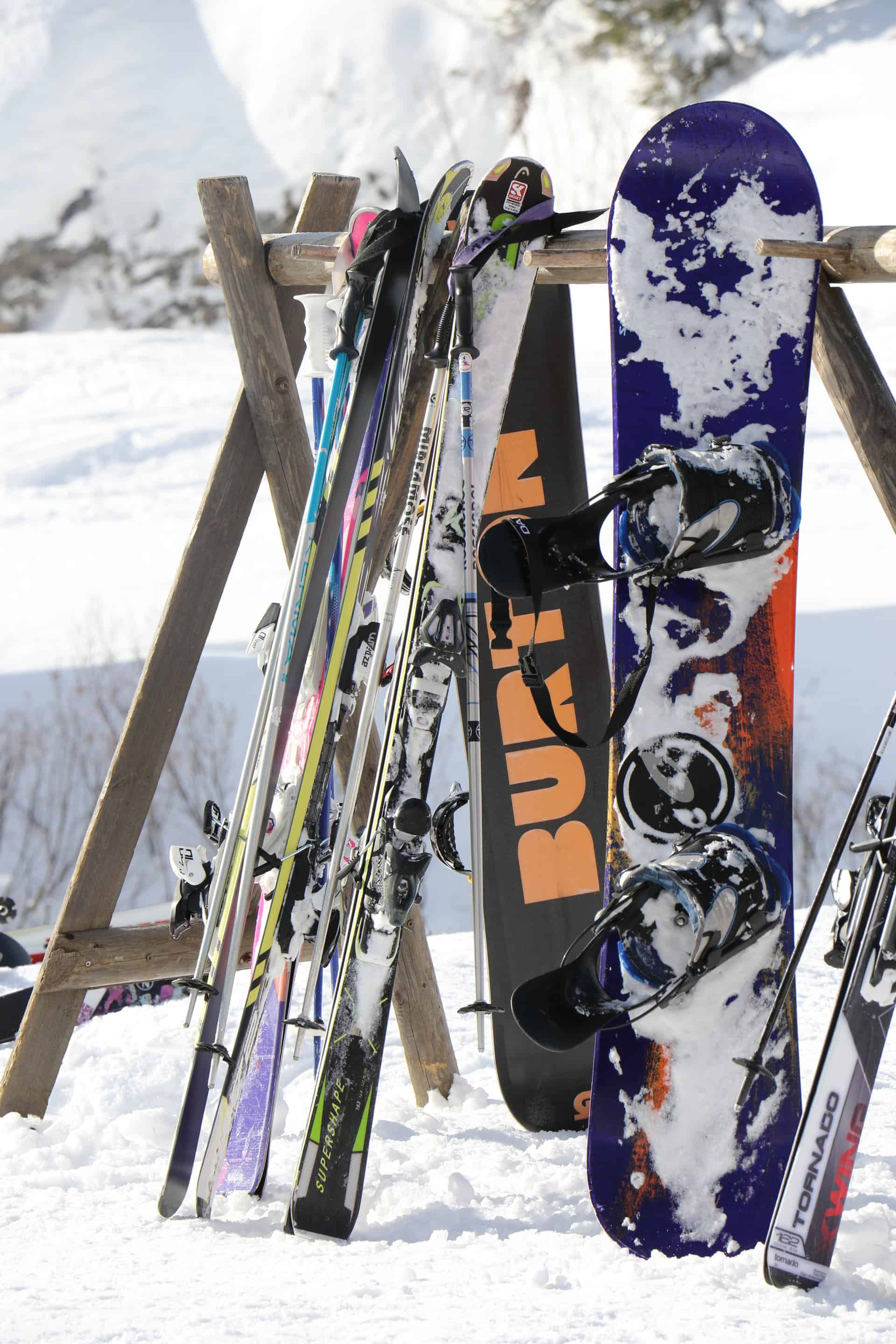 skis and snowboards resting against a pole