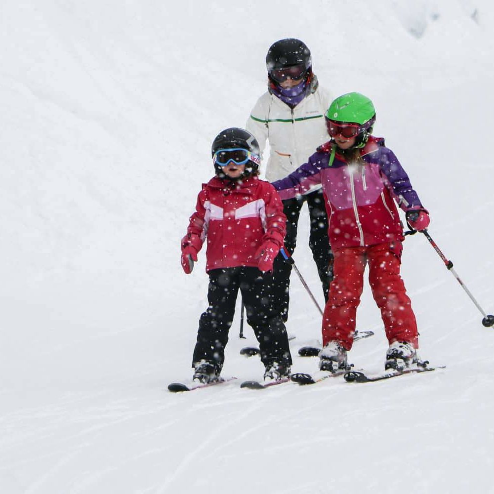 Mum and young children skiing